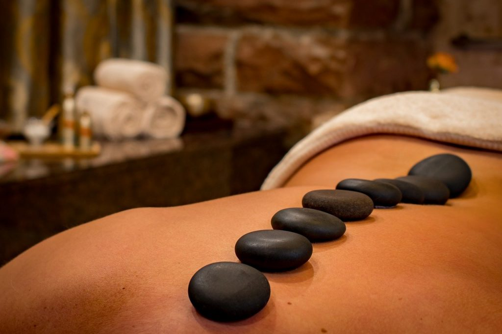 How do hot stones provide a therapeutic massage?